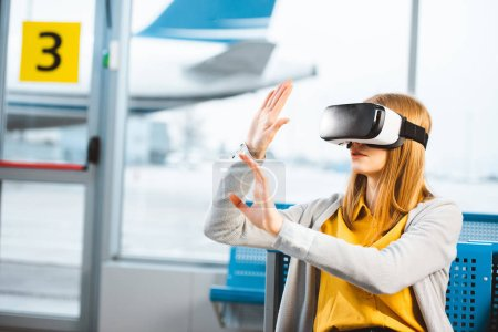 woman wearing virtual reality headset while sitting in airport