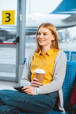 attractive woman holding disposable cup while sitting in airport