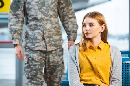 Photo pour Attrayant femme assise à l'aéroport avec vétéran sur fond - image libre de droit