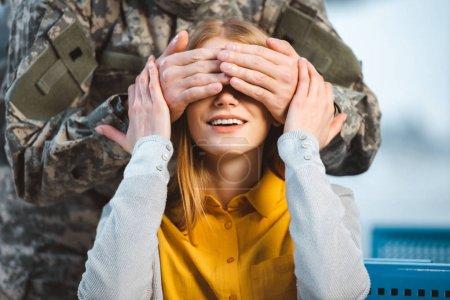 cropped view of veteran closing eyes of cheerful girlfriend