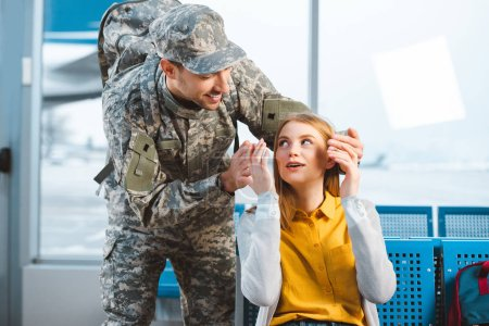 Photo pour Beau vétéran regardant petite amie surprise à l'aéroport - image libre de droit