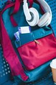 """Постер, картина, фотообои """"Наушники на рюкзак с паспорта и авиационные билеты в кармане"""""""