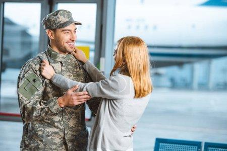 Photo pour Femme heureuse étreignant petit ami en uniforme militaire à l'aéroport - image libre de droit