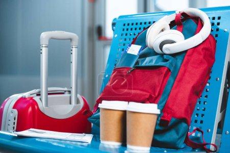 Foto de Auriculares mochila cerca de vasos de papel y equipaje en el aeropuerto - Imagen libre de derechos