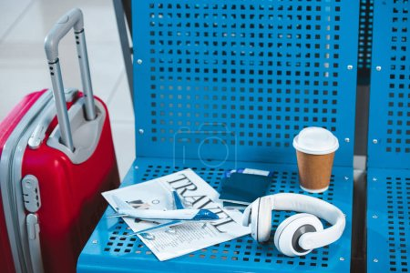 plane model on travel newspaper near paper cup and suitcase in airport