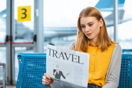 beautiful woman reading travel newspaper in departure lounge