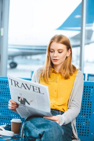 attractive woman reading travel newspaper in departure lounge