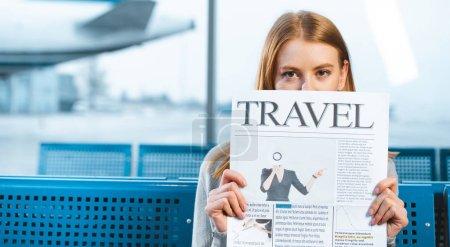 Photo pour Femme couvrant le visage avec le journal de voyage dans la salle d'attente - image libre de droit