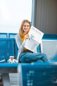 attractive woman smiling while holding travel newspaper in departure lounge