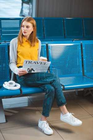 attractive woman reading newspaper near headphones in airport