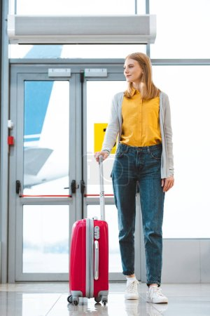 attractive woman standing with baggage in airport