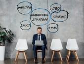 """Постер, картина, фотообои """"улыбаясь бизнесмен, сидя на стуле и использовать ноутбук в зале ожидания с маркетинговой стратегии иллюстрации на стене"""""""