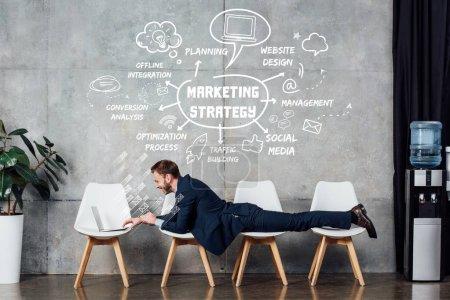 Photo pour Homme d'affaires couché sur des chaises et utilisant un ordinateur portable dans la salle d'attente avec illustration de stratégie de marketing sur le mur - image libre de droit