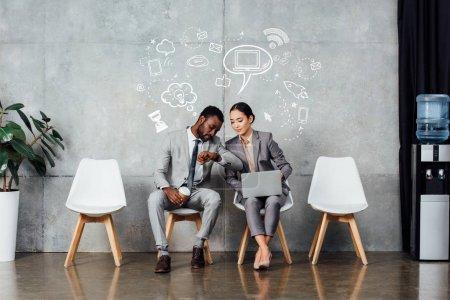 Foto de Colegas multiétnicas con ordenador portátil y café sentado y comprobación de tiempo en el reloj en la sala de espera con iconos de redes sociales en la pared - Imagen libre de derechos