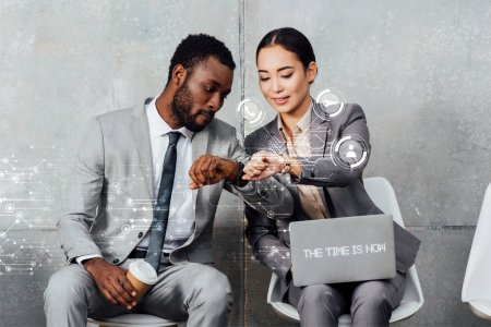 Photo for Multiethnic colleagues with laptop and coffee sitting and looking at smartwatches in waiting hall with the time is now lettering on laptop and notifications icons - Royalty Free Image