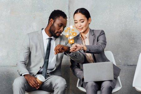 Photo pour Collègues multiethniques avec ordinateur portable et café assis et regardant smartwatches dans la salle d'attente avec des icônes de notifications de médias sociaux - image libre de droit