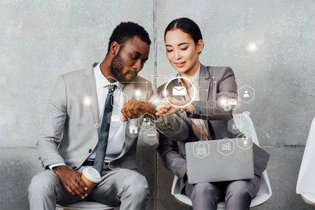 Photo pour Collègues multiethniques avec ordinateur portable et café assis et regardant smartwatches dans la salle d'attente avec des icônes de notifications - image libre de droit
