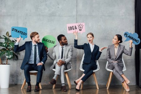Photo for Happy multiethnic businesspeople holding speech bubbles with idea, success, planning and strategy lettering while sitting in waiting hall - Royalty Free Image