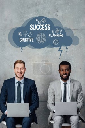 Photo for Smiling multiethnic businessmen looking at camera and using laptops in waiting hall with speech bubble illustration with creative, success and planning lettering - Royalty Free Image