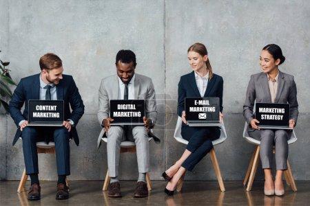 Photo pour Des gens d'affaires multiethniques souriants assis sur des chaises et tenant des ordinateurs portables avec du contenu, du marketing numérique et électronique et des lettres de stratégie de marketing sur les écrans dans la salle d'attente - image libre de droit