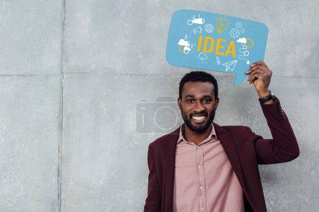 Foto de Empresario informal afroamericano sonriente mirando a cámara y manteniendo la burbuja del discurso con el deletreado de la idea - Imagen libre de derechos