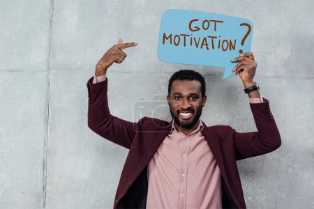 Photo for Smiling african american casual businessman looking at camera and pointing with finger at speech bubble with got motivation question - Royalty Free Image