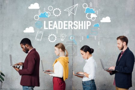 Photo pour Hommes d'affaires occasionnels multiethniques utilisant des ordinateurs portables tout en faisant la queue dans la salle d'attente avec illustration de leadership sur le mur - image libre de droit