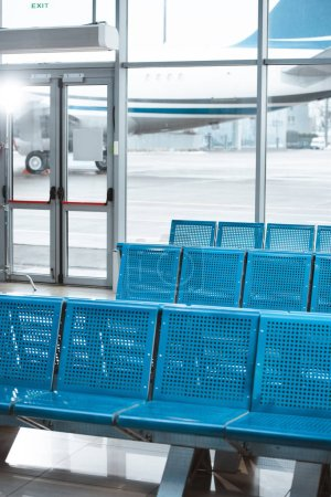 Photo for Empty departure lounge with blue metallic seats in airport - Royalty Free Image