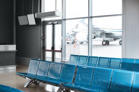 Photo for Empty waiting hall with blue metallic seats in airport - Royalty Free Image