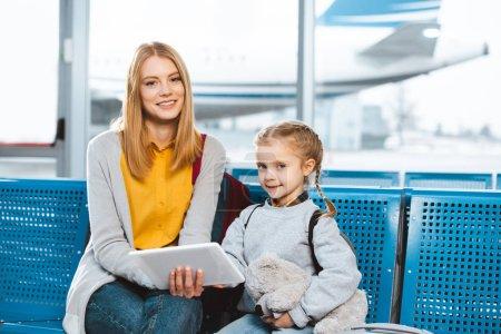 Photo pour Belle mère tenant la tablette numérique et assis dans l'aéroport avec fille - image libre de droit