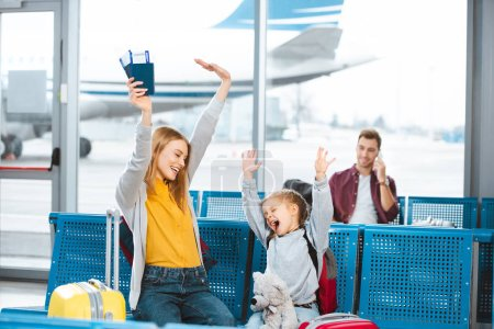 Photo for Selective focus happy mother and daughter holding hands above head and smiling in airport with man on background - Royalty Free Image