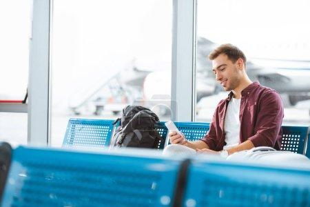 Photo pour Homme joyeux tenant smartphone tout en étant assis dans le salon de départ - image libre de droit