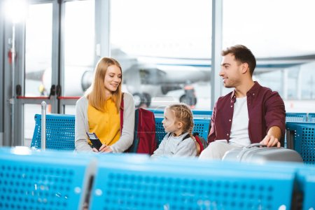 happy mother looking at daughter while sitting in waiting hall  with husband