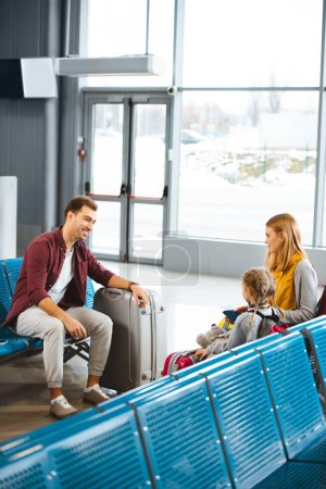mother sitting with daughter and looking at smiling husband in airport