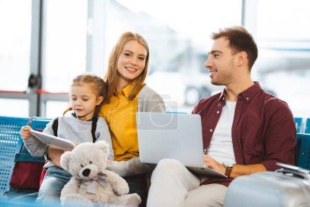 Photo pour Mignonne fille tenant une tablette numérique près de mère et assis près de père avec ordinateur portable à l'aéroport - image libre de droit