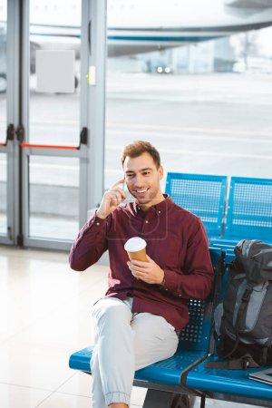Photo pour Heureux homme parler sur smartphone et tenant la tasse de papier à la main en aéroport - image libre de droit