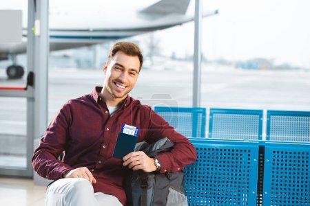 Photo pour Sourire de passeport holding homme avec billet d'avion près de sac à dos dans la salle d'attente - image libre de droit