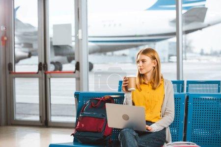 Photo pour Belle femme assis avec ordinateur portable et maintenant gobelet jetable en main en aéroport - image libre de droit