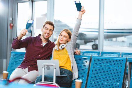 Photo for Happy girlfriend holding passport above head near smiling boyfriend in airport near luggage - Royalty Free Image