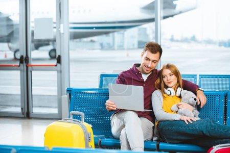 happy boyfriend holding laptop near girlfriend with teddy bear in departure lounge