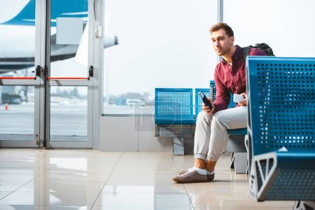 Photo for Handsome man holding smartphone and passport while sitting in departure lounge - Royalty Free Image