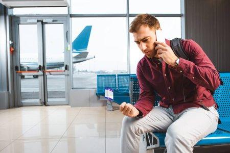 Photo pour Homme parle sur smartphone tout en étant assis dans la salle d'attente - image libre de droit