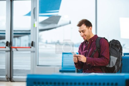 cheerful man using smartphone and smiling while waiting in departure lounge