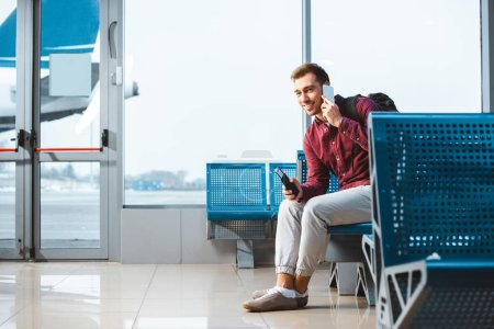 cheerful man talking on smartphone while sitting in departure lounge