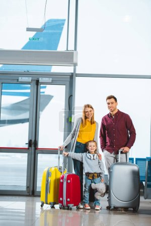 Photo for Happy family standing near baggage and smiling in waiting hall - Royalty Free Image