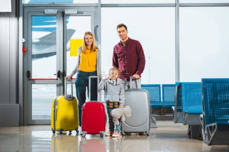 Photo for Cheerful family standing with luggage in waiting hall of airport - Royalty Free Image