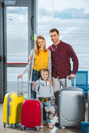 Photo pour Famille heureuse debout avec bagages dans le salon de départ - image libre de droit