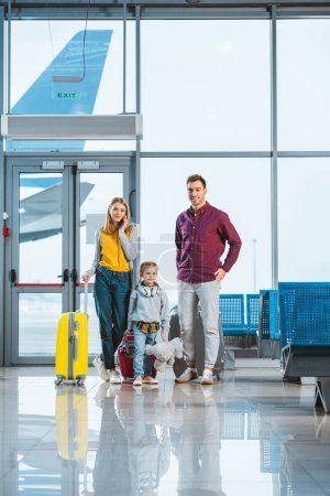 adorable child holding teddy bear and standing between mother and father in departure lounge