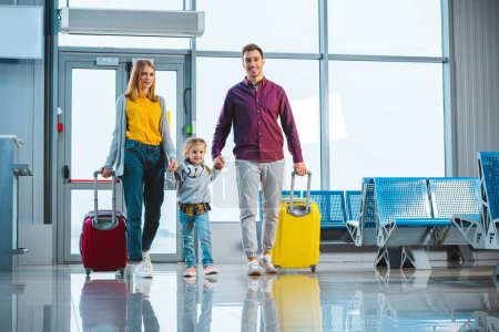Photo for Cheerful husband and wife holding hands with cute daughter and standing with suitcases - Royalty Free Image