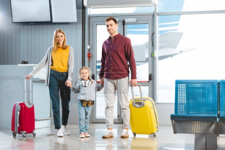 Photo for Happy mom and dad holding hands with daughter and standing with suitcases near gate in airport - Royalty Free Image